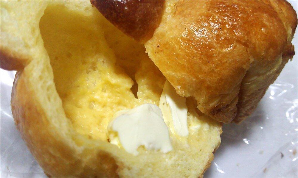 ブリオッシュを包丁で半分に切った断面、空洞の中身は黄色っぽく、底にはクリームチーズが入っている